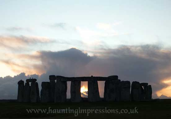 Stonehenge with crow - sun sets behind Sarsens